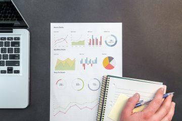 mão sobre cadernos de finanças e gráficos